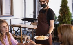 The waitress works in a restaurant in a medical mask, gloves during coronavirus pandemic. Representing new normal of service and safety. Taking orders, serving drinks and food. Keeps distance.